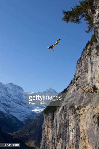 man is jumping of a cliff and falling down stock photo