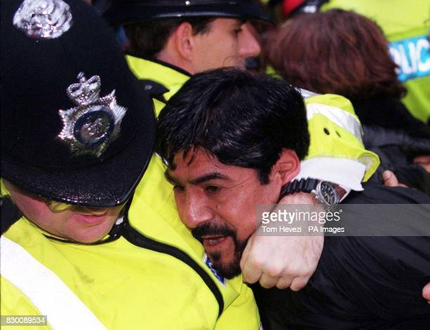 A man is led away by police this afternoon at the anti Pinochet protest outside the London Clinic where it is believed the former Chilean dictator is...
