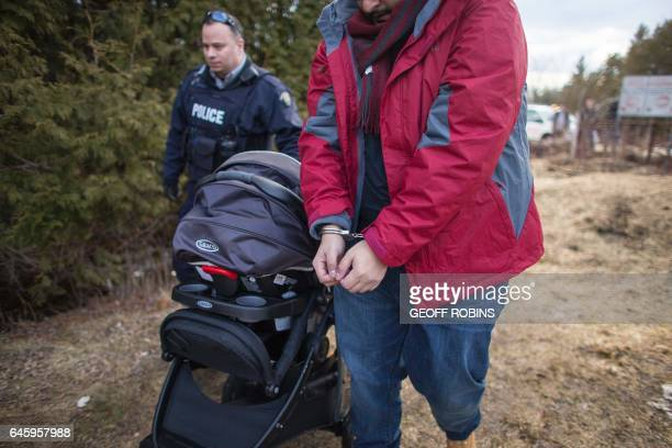 A man is led away in handcuffs by the RCMP after he his wife and baby illegally crossed the CanadaUS border near Hemmingford Quebec February 27 2017...