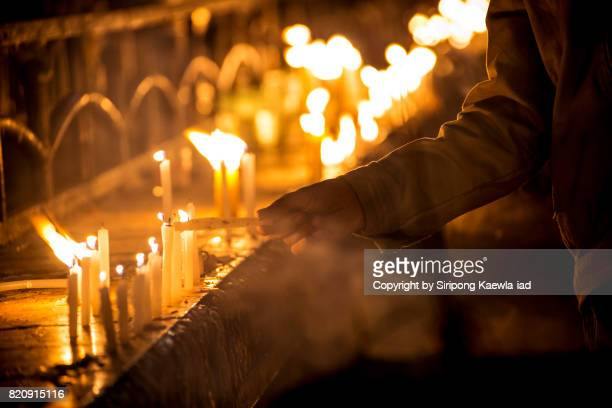 A man is lighting up a candle in his hand before start praying at the Kyaiktiyo Pagoda, Myanmar.