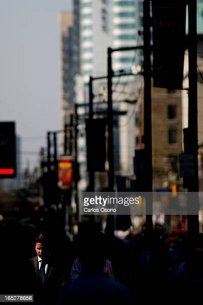 A man is lit with a ray of sunshine as he walks on King St W just west of Bay Street in Toronto's Financial district KPMG report gives Toronto high...