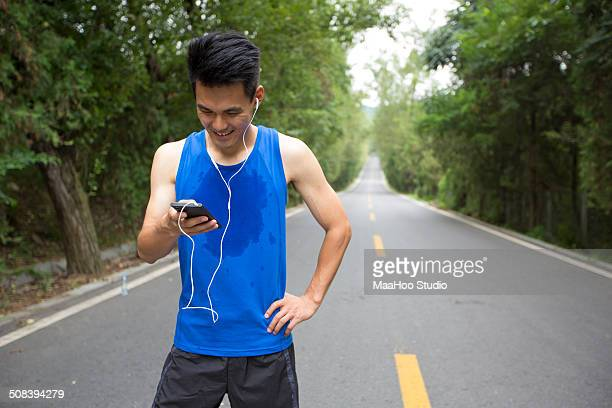Man is looking at smartphone after exercise