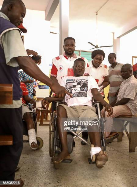 A man is moved in a wheechair as he awaits treatment by medical staff at the Secondary Hospital at Be Lome on October 19 after he was shot and...
