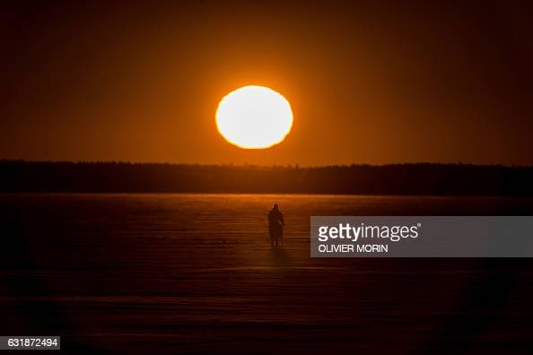 TOPSHOT A man is on his way for icefishing on January 17 2017 at sunrise on the frozen sea in Vaasa by 15°C / AFP / OLIVIER MORIN