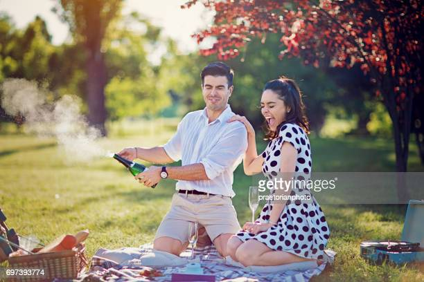 Man is opening champagne at the picnic in the park