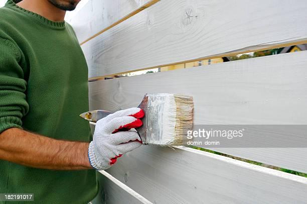 Mann Malerei und Pinsel Holz-Zaun auf Weiß