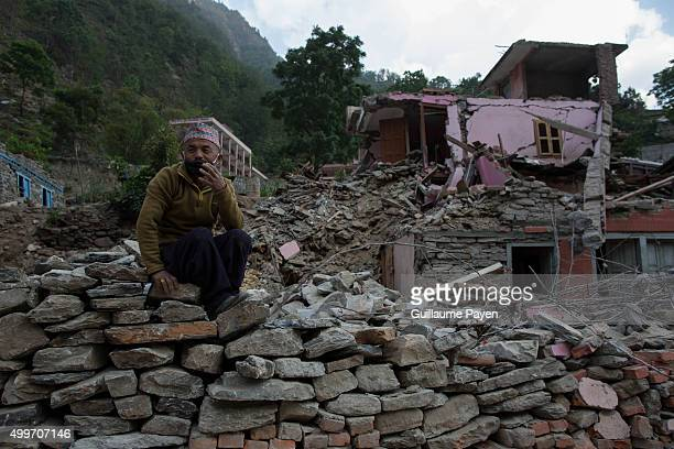 A man is pictured as he collect entire brick in order to build his house behind him on the Araniko Road near the Kobani Village Isolated Nepalese...