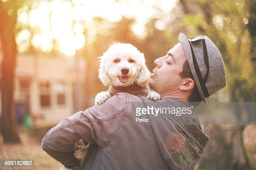 Man is playing in the park with a beautiful dog