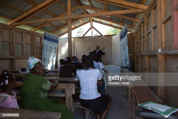 PortauPrince Haiti December 09 2012 A man is preaching inside a barrack that is a improvisational church in the refugee camp Parc Colofe in...