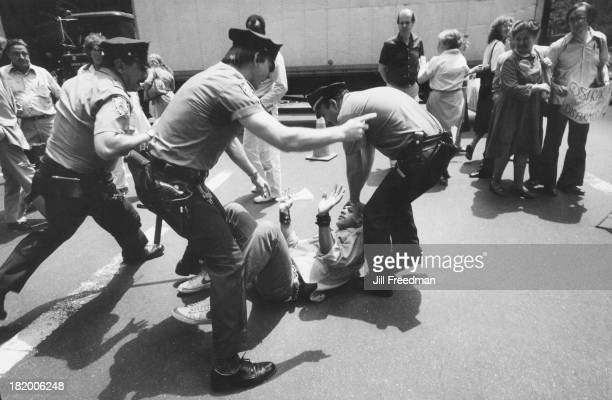 A man is pulled down to the floor by three police officers in Midtown Manhattan New York City 1982