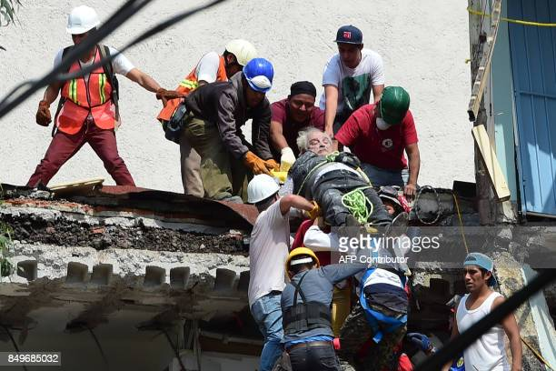 TOPSHOT A man is pulled out of the rubble alive following a quake in Mexico City on September 19 2017 A powerful earthquake shook Mexico City on...