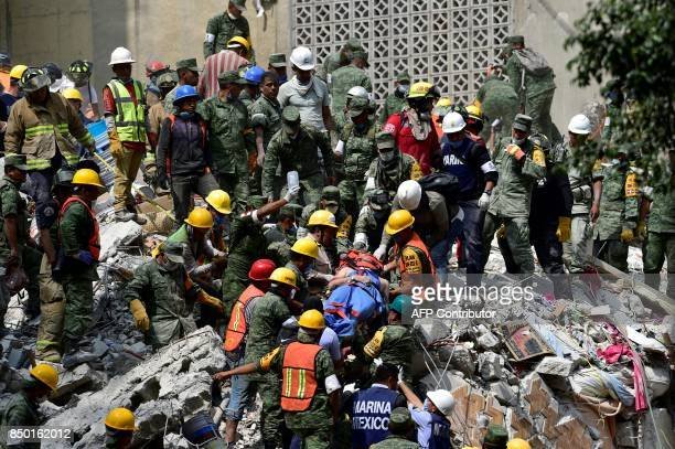TOPSHOT A man is pulled out of the rubble alive in Mexico City on September 20 2017 as the search for survivors continues a day after a strong quake...