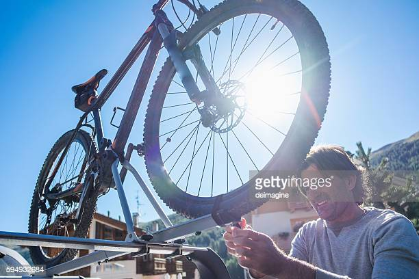Man is putting mountain bike on roof car