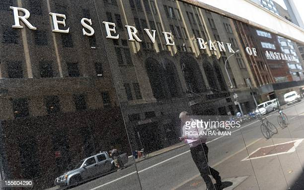 A man is reflected as he walks past the sign of the Reserve Bank of Australia office at the financial district in central Sydney on November 6 2012...