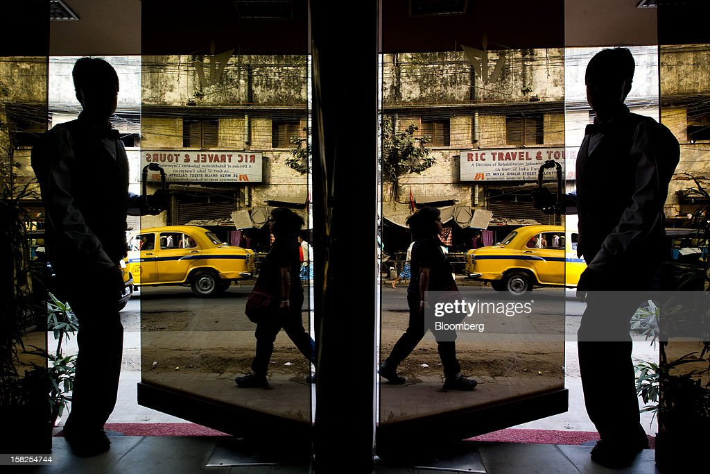 'BEST PHOTOS OF 2012' (): A man is reflected in a mirror as he enters a hotel in Kolkata, India, on Wednesday, Feb. 8, 2012. India's economy will probably expand 6.9 percent in the year ending in March, the government said on Feb. 7, less than the median estimate of 7 percent in a Bloomberg survey. Photographer: Brent Lewin/Bloomberg via Getty Images