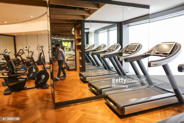 A man is reflected in a mirror inside a gym at The World Towers a luxury residential project developed by Lodha Developers Ltd in Mumbai India on...