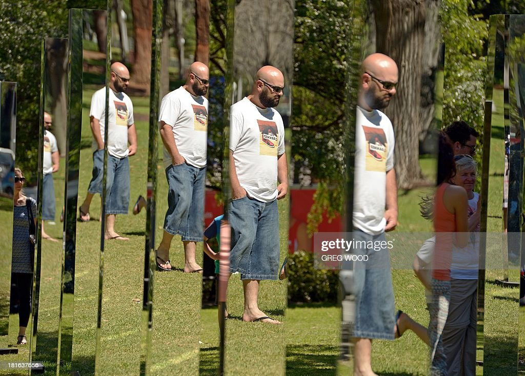 A man is reflected in a number of the mirrors that make up the installation 'Field' from Art & About Sydney on September 23, 2013. Field, developed by New Zealand architecture collective 'Out of the Dark', is a mesmerising maze of mirrors on 81 posts designed to be a place of literal reflection where the perspective is ever-changing, encouraging curious passers-by. AFP PHOTO / Greg WOOD