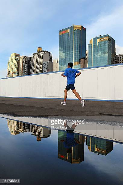 A man is reflected in a puddle of water as he jogs past the Barangaroo redevelopment project in front of the central business district in Sydney...