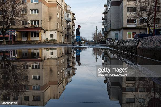 A man is reflected in a puddle of water as he walks down a street in the city of Zimnicea Romania approximately 130km southwest of the capital...
