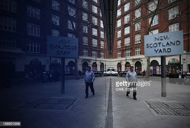 A man is reflected in a window as he walks past a sign for New Scotland Yard the headquarters of the Metropolitan Police in central London on January...