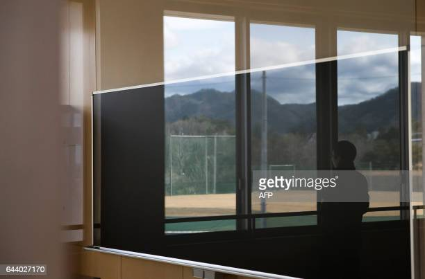 A man is reflected in a window of Narahamachi elementary school in Naraha Fukushima Japan on February 23 2017 The school is scheduled to reopen in...