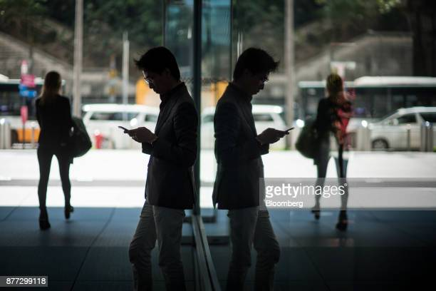 A man is reflected in a window while using a smart phone in Hong Kong China on Wednesday Nov 22 2017 Hong Kong's benchmark equity gauge rose above...