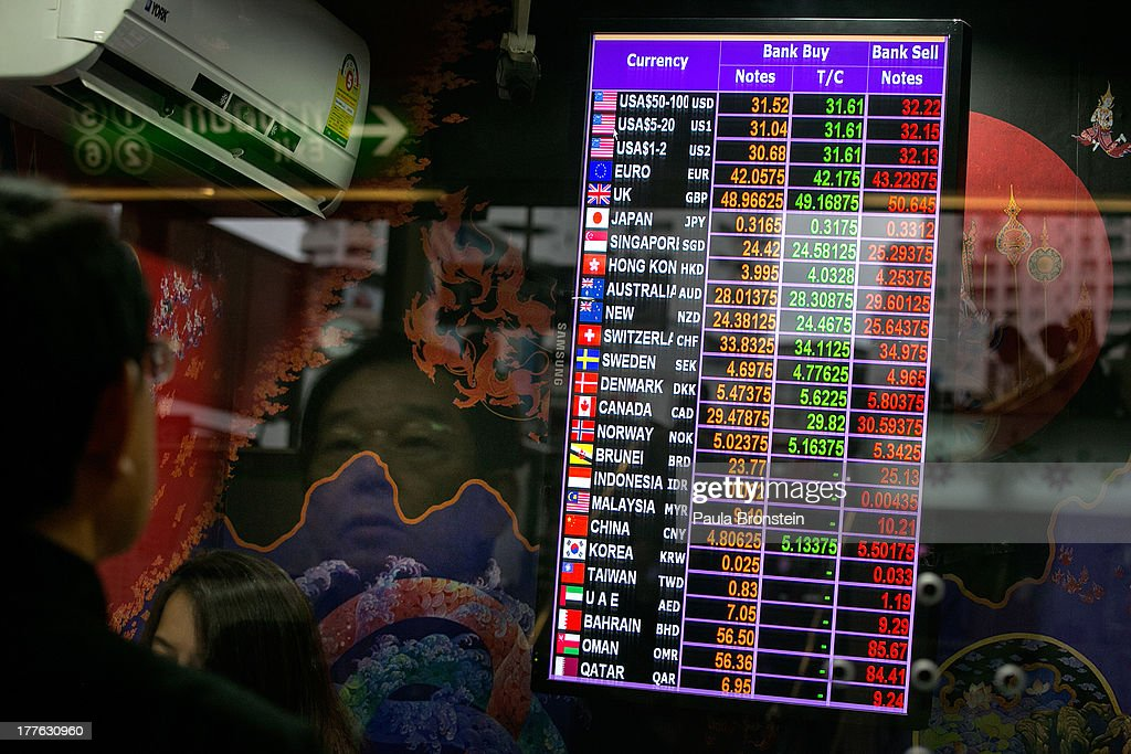 A man is reflected in the window of a money exchange bank kiosk showing the various currencies on August 23, 2013 in Bangkok, Thailand. The local currency dropped to its lowest level since August 2010. Against the US dollar the Thai baht fell to 32.09/32.13 dropping about 5% this year.