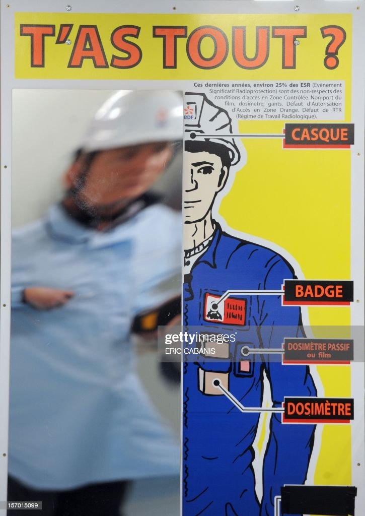 A man is reflected on a board which mentions the security measures as he enters the Golfech nuclear power plant, southwestern France, on November 27, 2012. The slogan reads : 'Got everything ?'. CABANIS