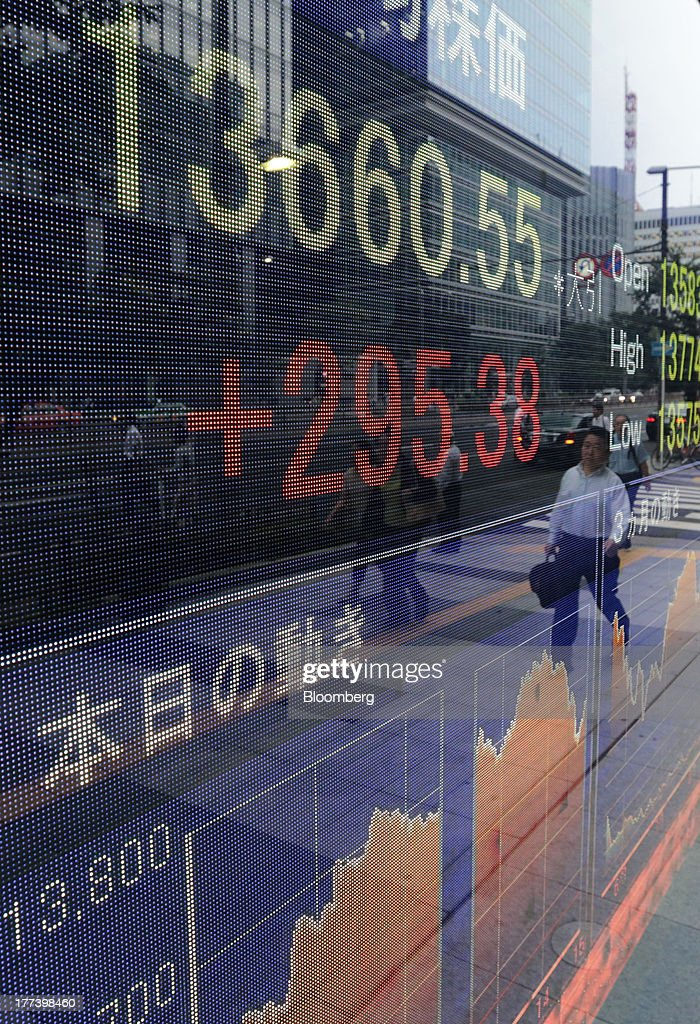 A man is reflected on an electronic monitor displaying the closing figure of the Nikkei 225 Stock Average outside a securities firm in Tokyo, Japan, on Friday, Aug. 23, 2013. Japanese shares rose, with the Topix index halting three days of losses, as exporters advanced after the yen weakened against the dollar. Photographer: Yuriko Nakao/Bloomberg via Getty Images