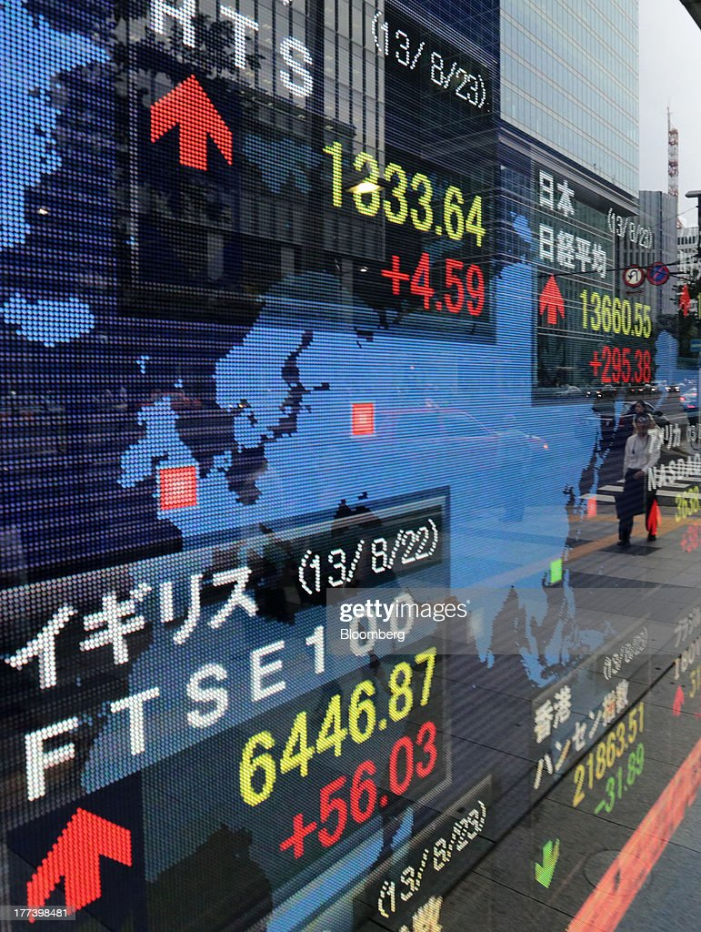 A man is reflected on an electronic monitor displaying the closing figure of the Nikkei 225 Stock Average, right, outside a securities firm in Tokyo, Japan, on Friday, Aug. 23, 2013. Japanese shares rose, with the Topix index halting three days of losses, as exporters advanced after the yen weakened against the dollar. Photographer: Yuriko Nakao/Bloomberg via Getty Images