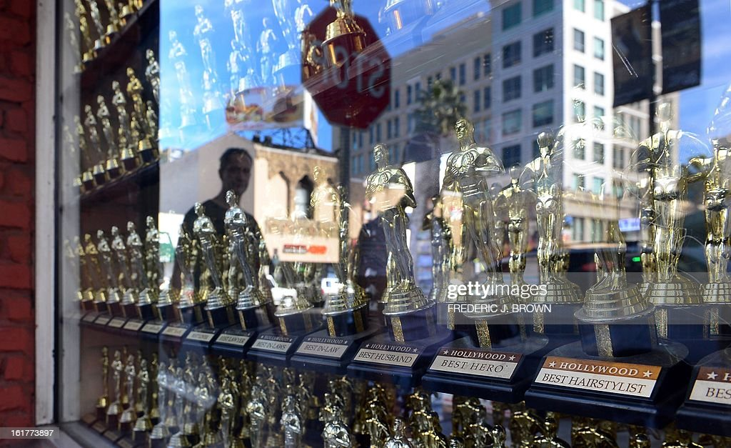 A man is reflected on the window of a retail shop selling mini statuettes like those presented to winners of the Academy Award on display and for sale along Hollywood avenue in Hollywood, California, on February 15, 2013. The 85th Academy Awards will take place in this heart of Hollywood neighborhood on Sunday, Februaty 24. AFP PHOTO / Frederic J. BROWN