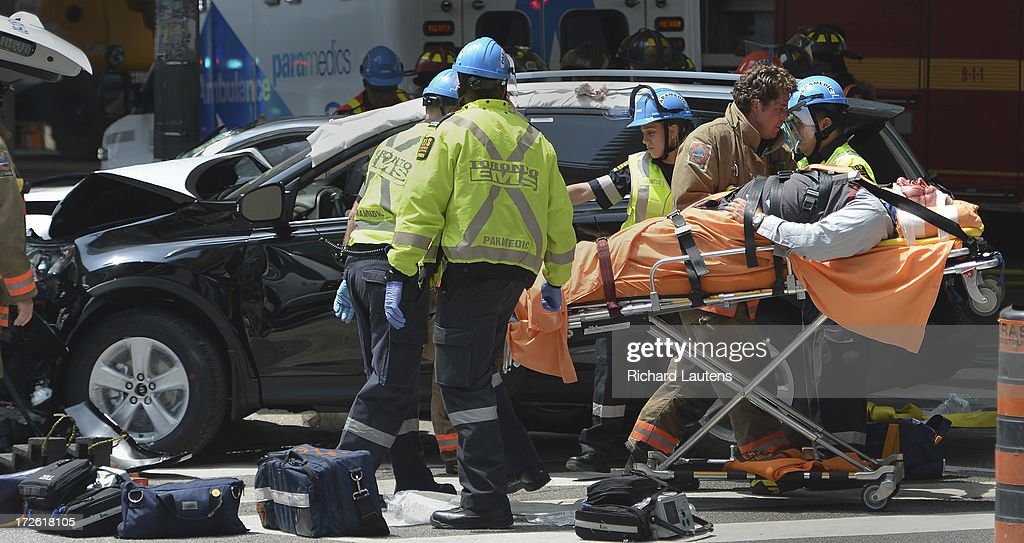 TORONTO, ON - JULY 3 - A man is removed from the dealer plated car by paramedics. A black crossover vehicle with dealer plates and a silver sedan from New Jersey collided at the intersection of Bay and Lakeshore in Toronto just after the noon hour. At least 5 were taken by stretcher into waiting ambulances. One man, in the driver seat of the sedan had to be cut out of the car with the jaws of life by the fire department.
