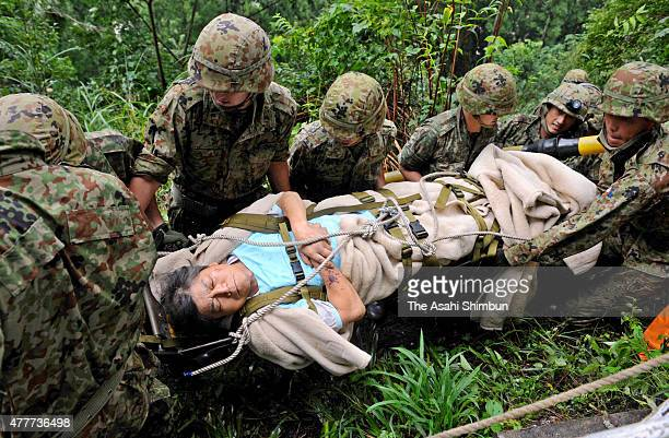 A man is rescued by Japan Ground SelfDefense Force members row after heavy rain triggered by Typhoon Talas is seen on September 4 2011 in Gojo Nara...