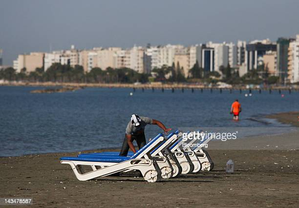 A man is seen cleaning sun loungers on the beach in Limassol Cyprus on Thursday April 26 2012 Cyprus's budget deficit widened to 63 percent of gross...