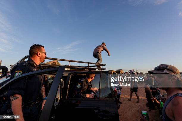 A man is seen climbing off the roof of a Police vehicle at the 2017 Deni Ute Muster on September 30 2017 in Deniliquin Australia He was ordered down...