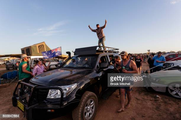 A man is seen climbing on the roof of a Police vehicle at the 2017 Deni Ute Muster on September 30 2017 in Deniliquin Australia He was soon ordered...
