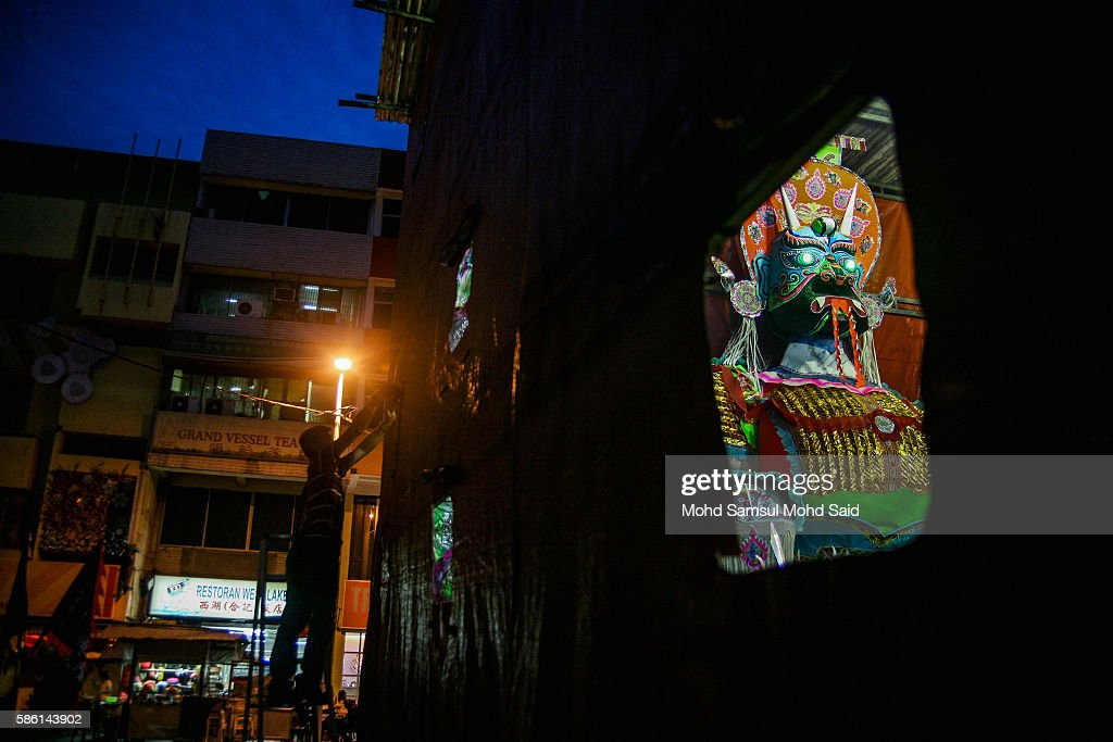 A man is seen do his work near the giant ghost (R) during Hungry Ghost Festival on August 5, 2016 in Kuala Lumpur, Malaysia. The Hungry Ghost Festival falls on the 15th day of the seventh lunar month. According to traditional Chinese belief, the seventh month in the lunar calendar is when restless spirits roam the earth. Many Chinese people make efforts to appease these transient ghosts, while feeding their own ancestors particularly on the 15th day, which is the Yu Lan or Hungry Ghost Festival.