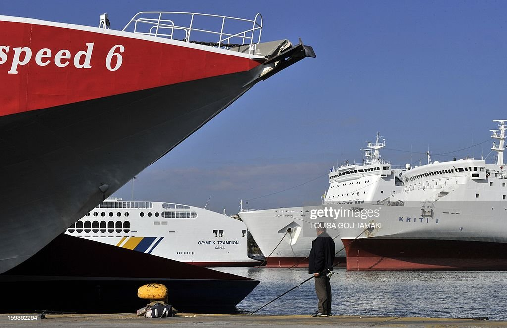 A man is seen fishing next to anchored ferries in the Piraeus harbour on October 24, 2011. Greek shipowners will pay taxes on their vessels registered abroad the first time in decades although their other fiscal advantages will remain unchanged, a source from the Merchant Marine Ministry said on January 11, 2013. An agreement between the government and the shipowners that will be part of the new tax bill the Greek parliament is expected to approve late on Friday night will alter a fiscal system virtually unchanged since 1955 said the source.