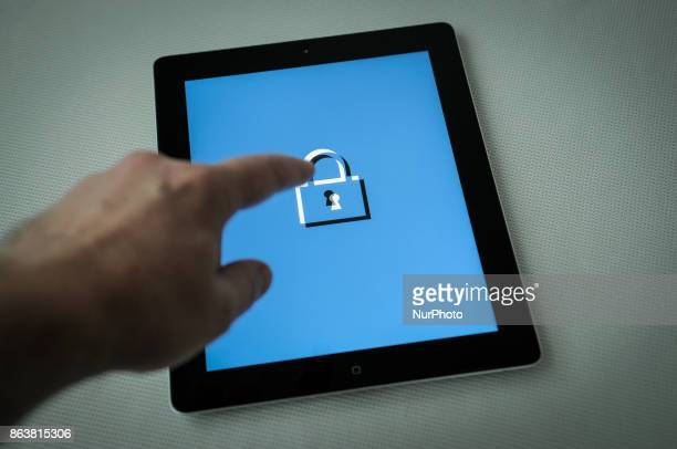 A man is seen handling a secured computer tablet in this photo illustration on Ocotber 20 2017