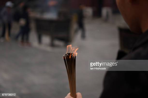 A man is seen holding burning incense sticks at the Lama Temple during the 'Tomb Sweeping Festival' on April 4 2017 in Beijing China
