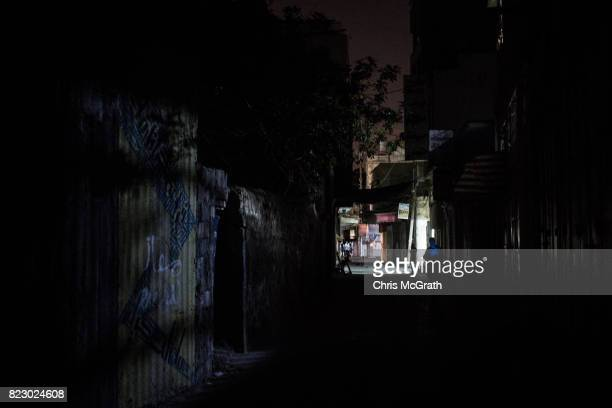 A man is seen illuminated by his cell phone as he walks in a darkened downtown street on July 22 2017 in Gaza City Gaza For the past ten years Gaza...