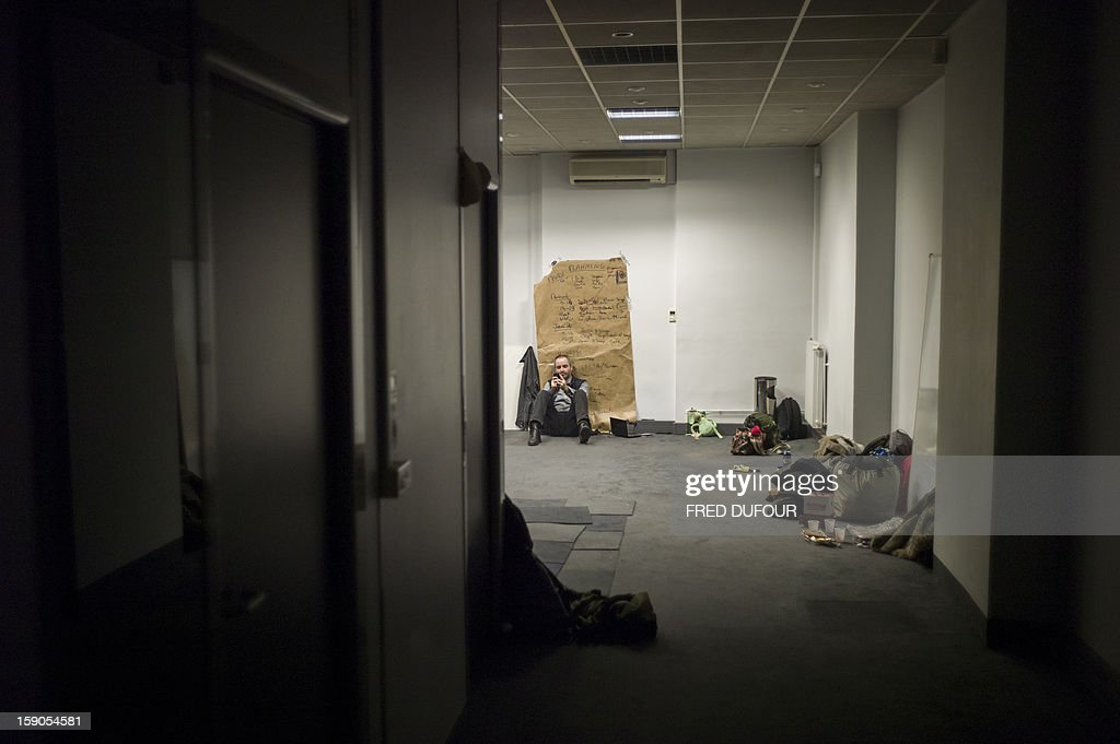 A man is seen in a room he occupied in a building requisitioned by French associations 'Jeudi Noir' ('Black Thursday') and 'Droit Au Logement', ('Right to Housing Association', DAL), on January 6 , 2013 in Paris. The building, situated in the 10th arrondissement of Paris is occupied since December 31, 2012. AFP PHOTO / FRED DUFOUR