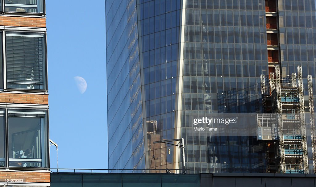 A man is seen in a window (LOWER L) in Lower Manhattan as One World Trade Center (R) rises under construction on October 22, 2012 in New York City. The Census Bureau reported last month that between 2000 and 2010 the downtown population grew by nearly 40,000 people, in spite of the September 11 terrorist attacks at the World Trade Center. One World Trade Center is scheduled to open in 2014 at the symbolic height of 1,776 feet and will be the tallest building in the Western Hemisphere.