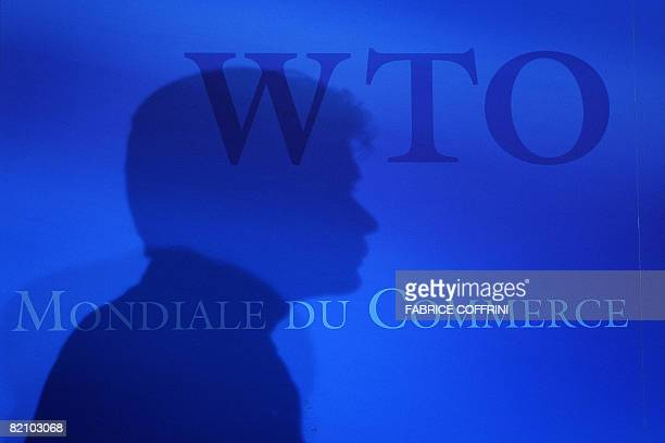 A man is seen in silhouette at the World Trade Organisation headquarters after crucial trade talks collapsed on July 29 in Geneva Efforts to forge a...
