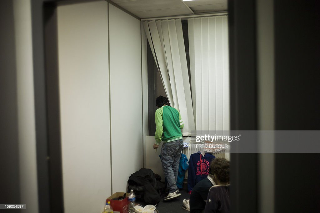 A man is seen in the room he occupied in a building requisitioned by French associations 'Jeudi Noir' ('Black Thursday') and 'Droit Au Logement', ('Right to Housing Association', DAL), on January 6 , 2013 in Paris. The building, situated in the 10th arrondissement of Paris is occupied since December 31, 2012.