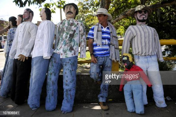 A man is seen next 'Ano viejo' dolls in the streets of Cali department of Valle del Cauca Colombia on December 31 2010 These dolls made of cardboard...