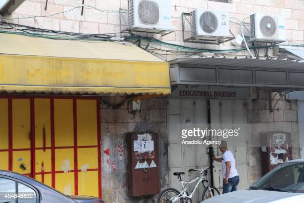 A man is seen next to shuttered stores during a strike which refers death of 16 years old Palestinian named Muhammed Abdulcelil Sinokrot killed by...