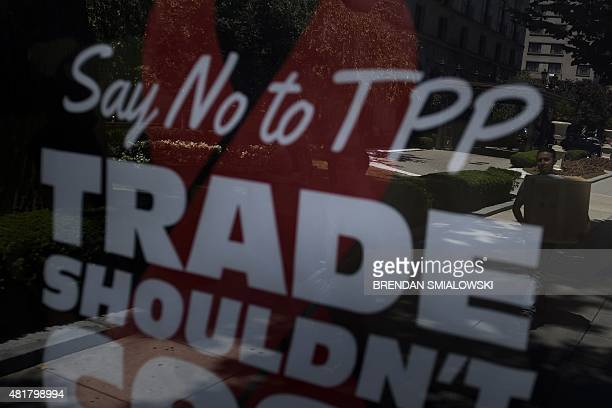 A man is seen reflected on a bus stop in an advertisement protesting the passage of the TransPacific Partnership in Washington DC on July 23 2015...