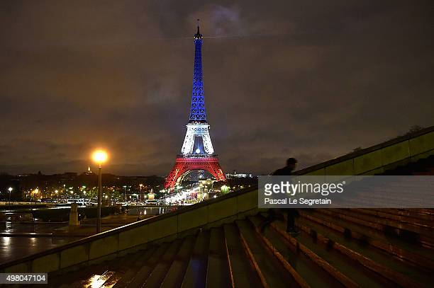 A man is seen running as the Eiffel Tower is illuminated in Red White and Blue in honour of the victims of Friday's terrorist attacks on November 20...