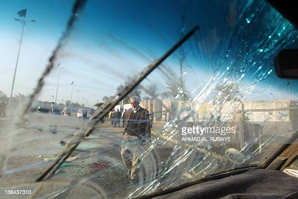 A man is seen through the shattered windshield of a car as he walks by blood and glass on the pavement after a boobytrapped motorcycle exploded near...